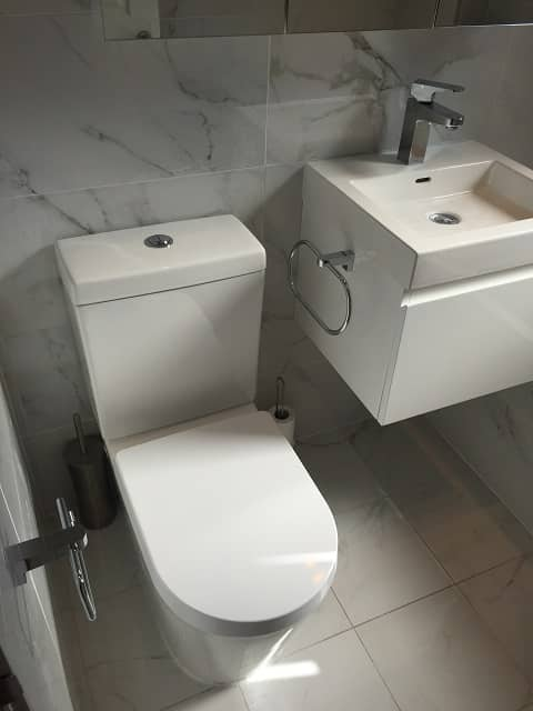 Left view of bathroom with toliet and sink. Tiled walls and floor.