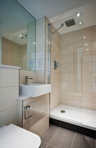 Sleek style of a modern bathroom. Large showerhead built into the ceiling of the shower, cream tiled walls and grey tiled floor.