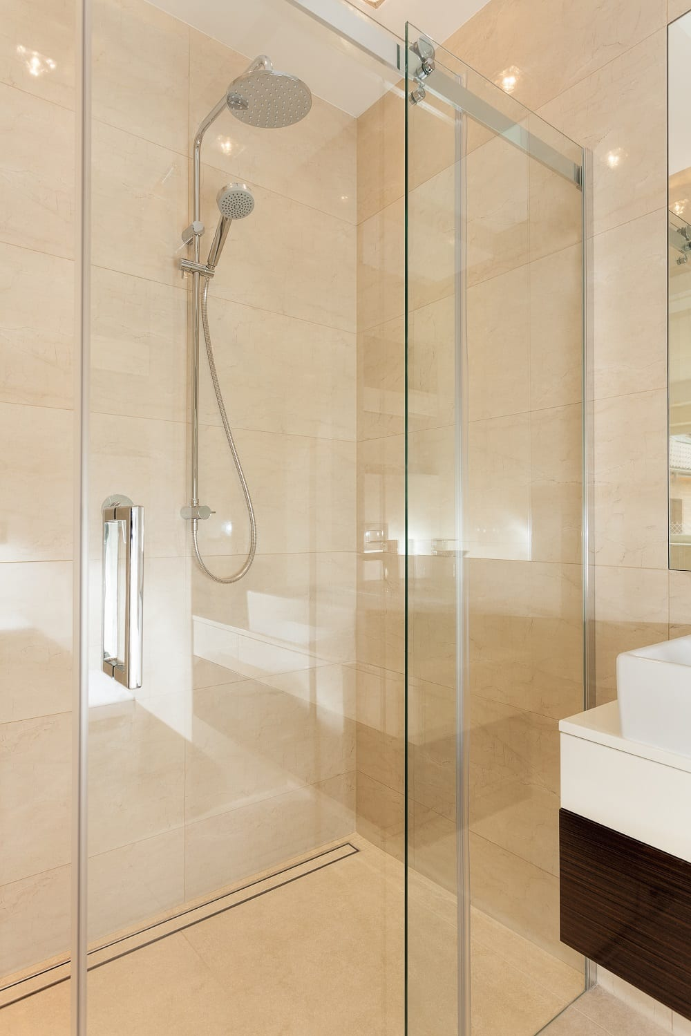Small ensuite showing shower with door open.
