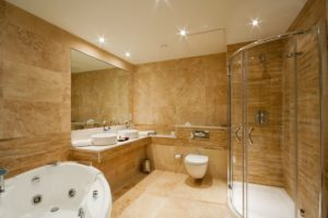 Elegant looking bathroom with corner shower, his and her sinks with large mirror, toilet and spabath