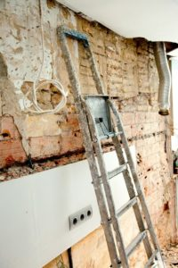 Exposed brickwork, electrical cable and extraction venting after demolition.
