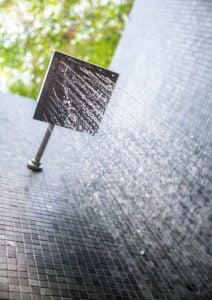 Outdoor rain showerhead with water coming down.